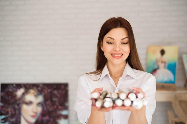Menina inspirada nova que escolhe o tubo da pintura no estúdio claro