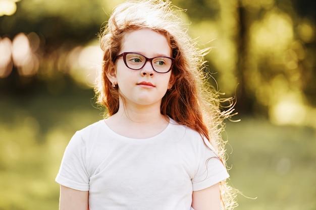 Menina inteligente de óculos no parque primavera.