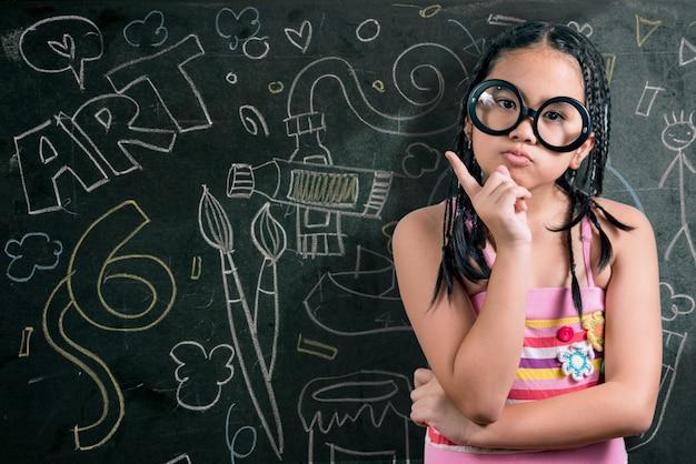 Menina inteligente sorrindo na frente de um quadro negro