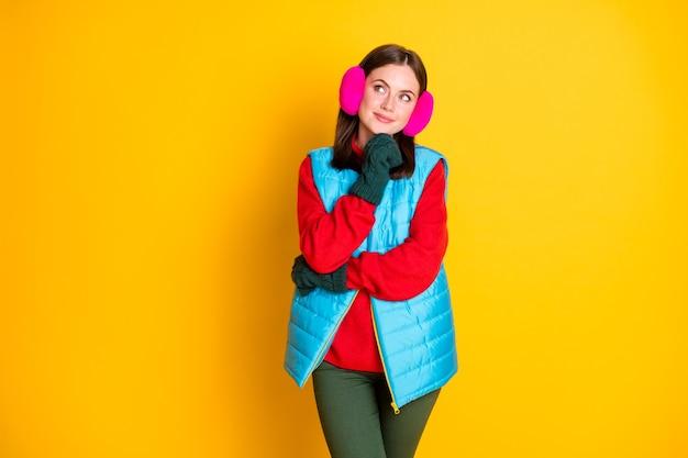 Menina interessada na foto tocar luvas verdes queixo olhar copyspace pensar pensamentos decidir férias de inverno planos usar calça azul rosa suéter isolado brilhante brilho cor de fundo