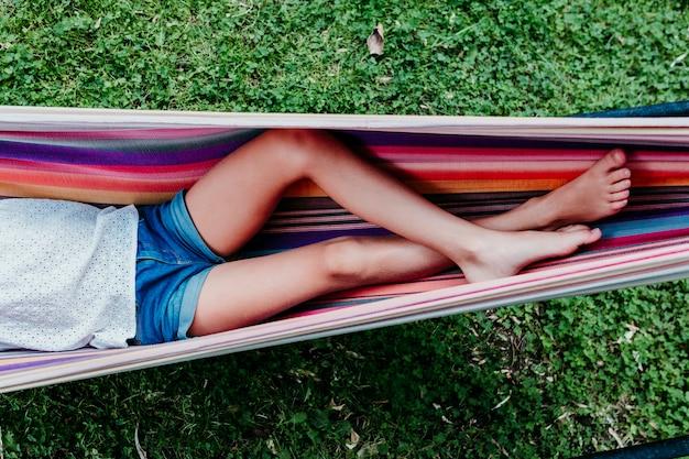 Menina irreconhecível adolescente deitado na rede colorida no jardim. relaxar e se divertir ao ar livre