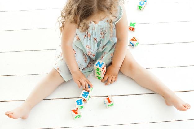Menina irreconhecível brincando com cubos abc dentro de casa