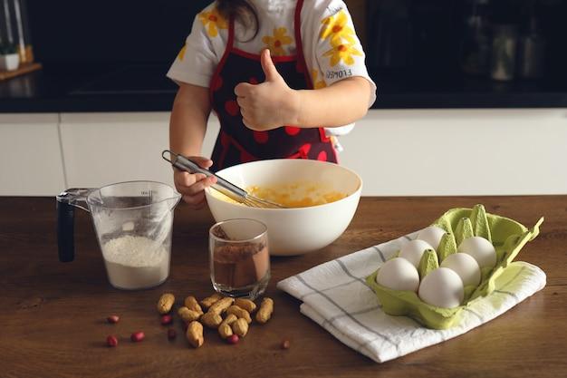 Menina irreconhecível de avental dentro de casa na cozinha sove a massa para um bolo ou muffins com cacau e nozes.