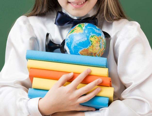 Menina irreconhecível, segurando a pilha de livro