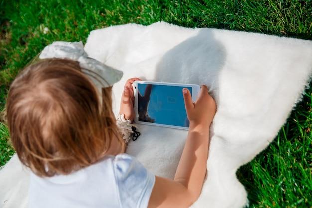Menina irreconhecível vestida de pólo branco e jeans, descalça deitada com o tablet sobre o cobertor de pele no parque.