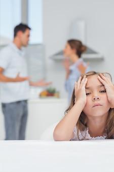 Menina irritada enquanto ouvia os brigas dos pais