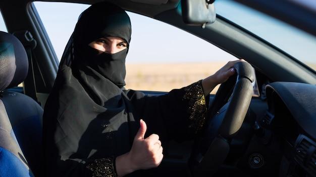 Menina islâmica mostrando aula de mão, levantando o polegar, sentada atrás do volante de um carro
