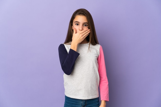 Menina isolada em fundo roxo cobrindo a boca com a mão