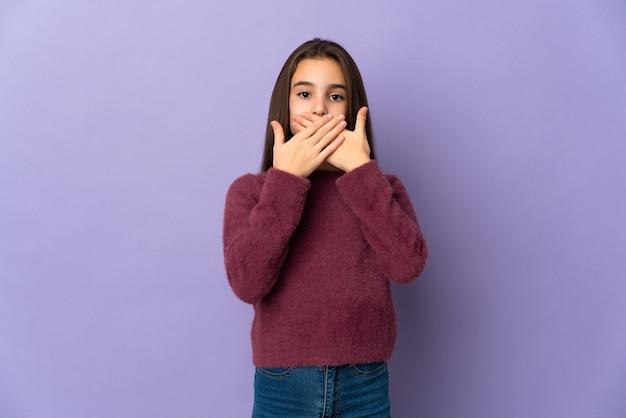 Menina isolada em fundo roxo cobrindo a boca com as mãos