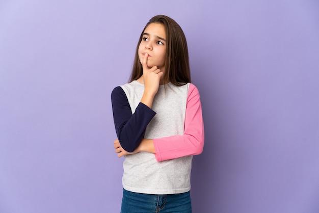 Menina isolada em fundo roxo tendo dúvidas enquanto olha para cima