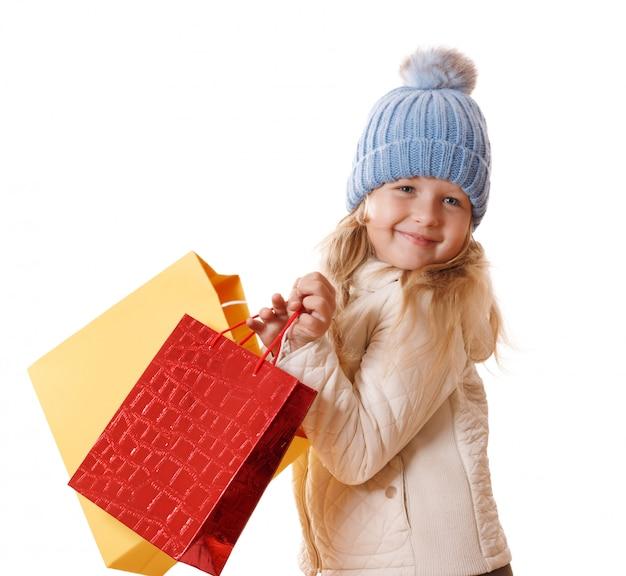 Menina isolada em um chapéu e um revestimento bege com sacos de papel.