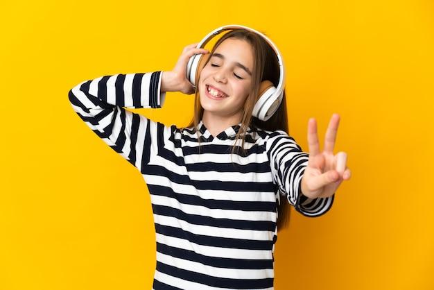 Menina isolada em um fundo amarelo ouvindo música e cantando