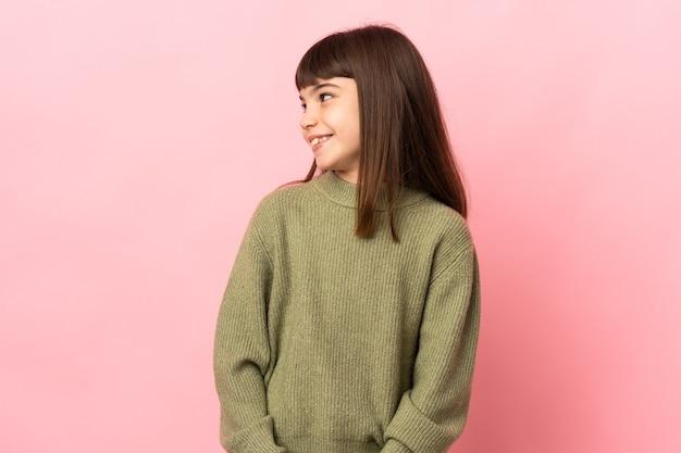 Menina isolada em um fundo rosa olhando para o lado e sorrindo