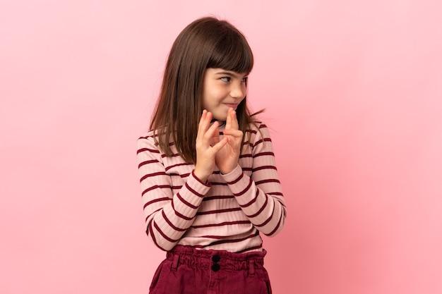 Menina isolada em um fundo rosa tramando algo