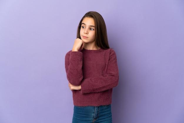 Menina isolada em um fundo roxo com expressão de cansaço e tédio
