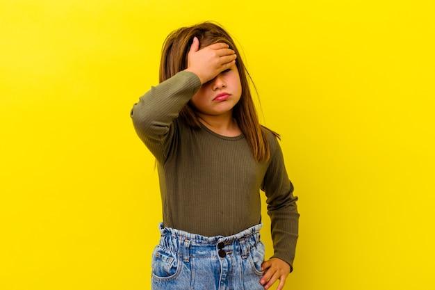 Menina isolada na parede amarela com dor de cabeça, tocando a frente do rosto