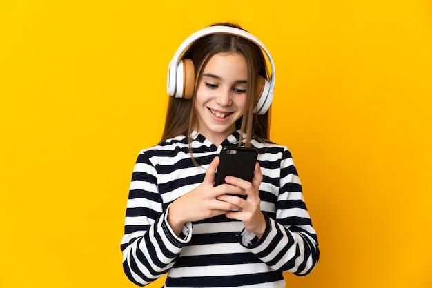 Menina isolada na parede amarela ouvindo música e olhando para o celular