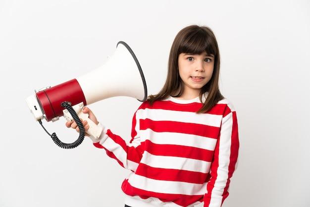 Menina isolada na parede branca segurando um megafone com expressão estressada