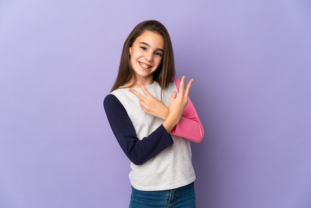 Menina isolada na parede roxa sorrindo e mostrando o sinal da vitória