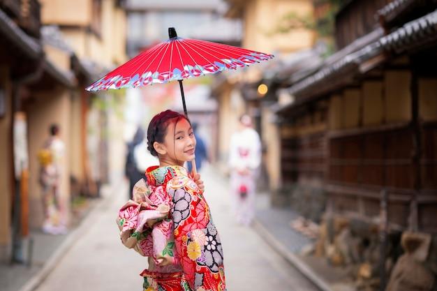 Menina japonesa a pé no antigo mercado de quioto