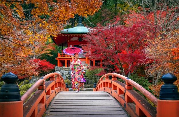 Menina japonesa no vestido tradicional de quimono andar na ponte vermelha no templo de daigoji