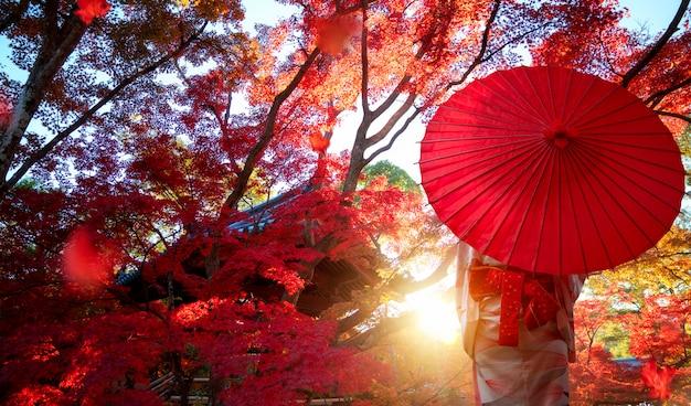 Menina japonesa no vestido tradicional de quimono viaja no parque vermelho de outono na cidade de kyoto, japão
