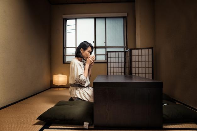 Menina japonesa senta-se em casa e bebe chá