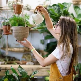 Menina jardineira regando planta em vaso, mulher, estudante florista, cuida das plantas domésticas no jardim doméstico