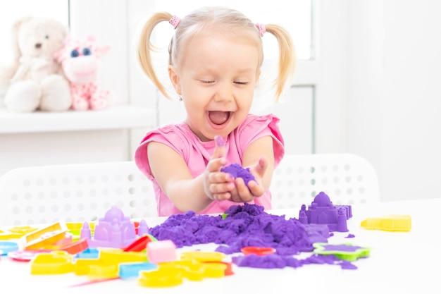 Menina joga areia cinética em quarentena. a menina bonita loura sorri e joga com areia roxa em uma tabela branca.