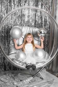 Menina joga em uma cadeira, uma tigela de vidro com bolas de prata. capa da rainha da neve.