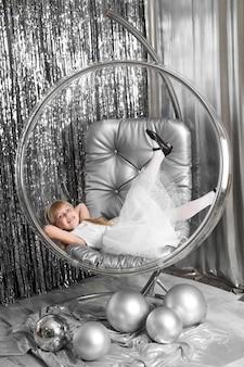 Menina joga em uma cadeira, uma tigela de vidro com bolas de prata