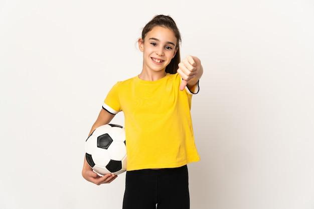 Menina jogador de futebol isolada no fundo branco, mostrando o polegar para baixo com expressão negativa