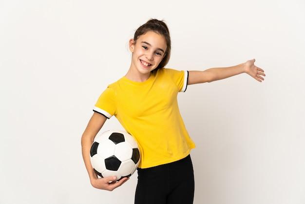 Menina jogadora de futebol, isolada no fundo branco, estendendo as mãos para o lado para convidar para vir