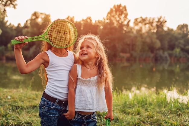 Menina jogando badminton com a irmã no parque de verão