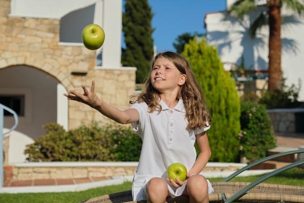 Menina jogando, brincando, fazendo malabarismos com maçãs verdes