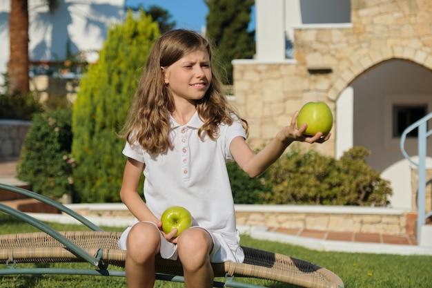 Menina jogando, brincando, malabarismo com maçãs verdes, dia ensolarado de verão