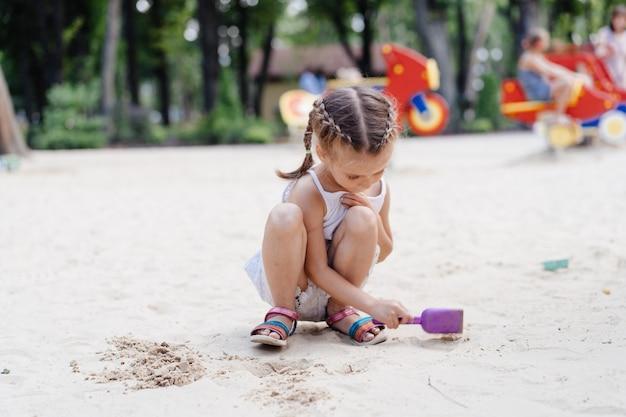 Menina jogando caixa de areia playground cavar areia pá construção figura de areia dia de verão. criança caucasiana feminino 5 anos divirta-se ao ar livre
