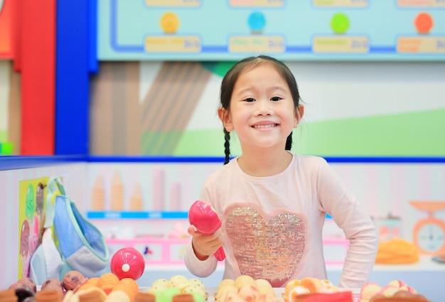 Menina jogando fingir como uma venda na sorveteria