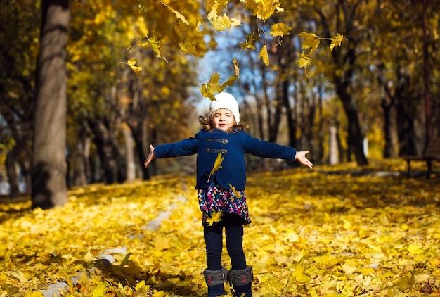 Menina jogando folhas de outono