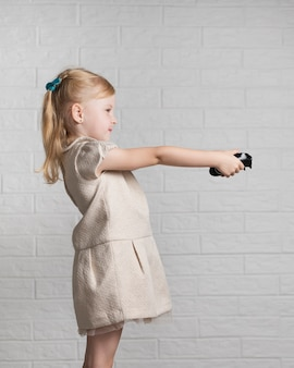 Menina jogando jogos digitais com joystick em casa
