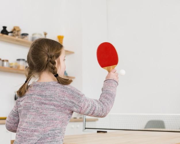 Menina jogando tênis de mesa dentro de casa