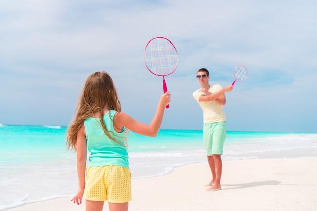 Menina jogando tênis de praia de férias com o pai