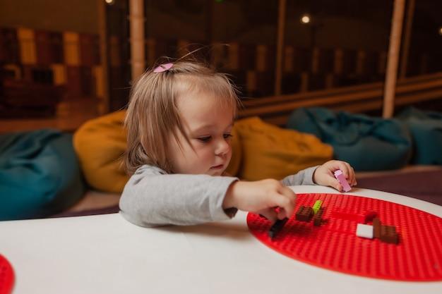 Menina jogando tijolos de brinquedo na mesa do centro de entretenimento infantil