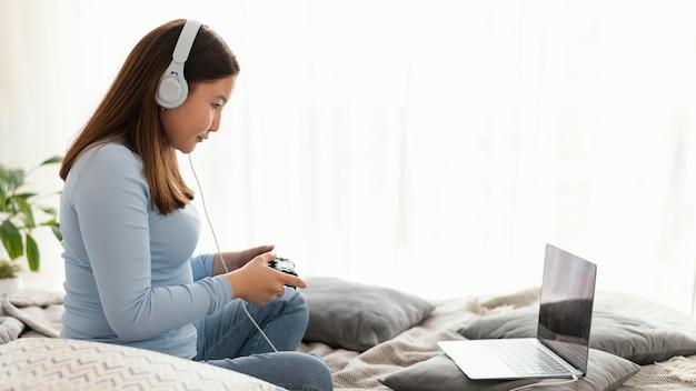 Menina jogando videogame com fones de ouvido