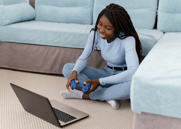 Menina jogando videogame com laptop