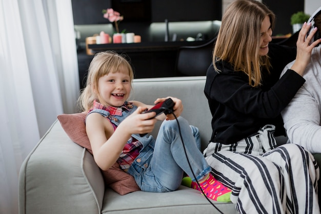 Menina jogando videogame perto de pais
