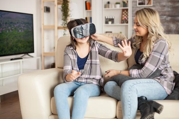 Menina jogando videogame usando óculos de realidade virtual, sentada no sofá ao lado de sua mãe.