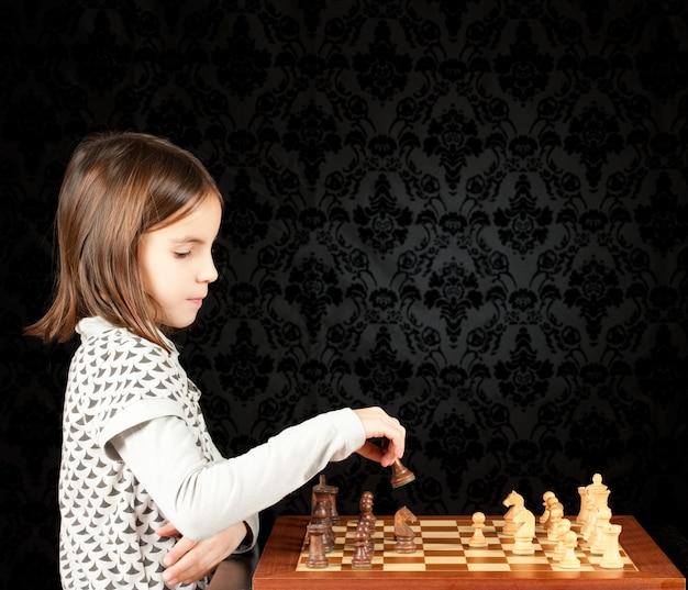 Menina jogando xadrez na parede vintage