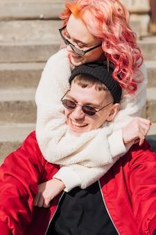 Menina jovem, abraçando, namorado, enquanto, sentar escada