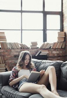 Menina jovem adolescente lendo um livro em casa